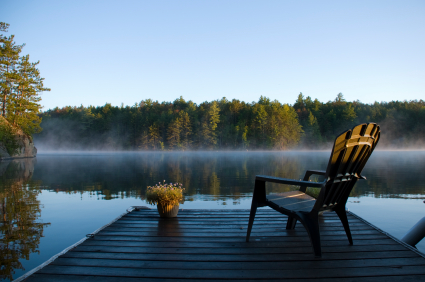 A chair on a dock facing a serene lake.
